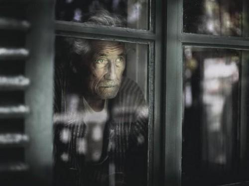 Anciano mirando a traves de la ventana