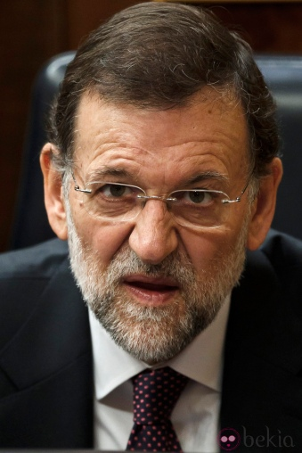 Spain's Prime Minister Mariano Rajoy talks with a party member, not seen, during a plenary session at the Spanish Parliament to approve the new conservative government's first batch of austerity measures, in Madrid, Wednesday, Jan. 11, 2012