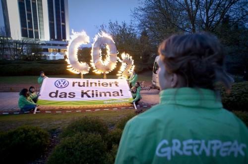 """Greenpeace activists protest with a burning CO2 sign in front of the CCH convention center in Hamburg one day ahead of the Volkswagen shareholders meeting. A banner also reads (in German): """"VW ruins the climate!"""" (VW ruiniert das Klima!"""") Greenpeace Aktivisten protestieren mit einem brennenden CO2 Zeichen, vor dem CCH (Congress Center Hamburg) in Hamburg, gegen die klimaschaedliche Modellpolitik des Volkswagenkonzerns. Auf einem Banner steht:""""VW ruiniert das Klima!"""". Am folgenden Tag findet die Volkswagen-Hauptversammlung im CCH statt."""