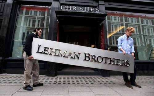 "LONDON, ENGLAND - SEPTEMBER 24: Two employees of Christie's auction house manoeuvre the Lehman Brothers corporate logo, which is estimated to sell for 3000 GBP and is featured in the sale of art owned by the collapsed investment bank Lehman Brothers on September 24, 2010 in London, England. The ""Lehman Brothers: Artwork and Ephemera"" sale will take place on September 29, 2010, on the second anniversary of the firm's bankruptcy, and comprises of artworks which hung on the walls of Lehman Brothers' offices in Europe. (Photo by Oli Scarff/Getty Images)"