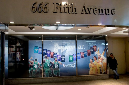 A man talks on his mobile phone outside the NBA Store at 666 Fifth Avenue in New York, U.S., on Friday, April 25, 2008. Carlyle Group, the world's second-largest private-equity firm, is poised to buy the retail portion of 666 Fifth Ave. building for $525 million in a transaction that would help the building's owner Jared Kushner repay debt, according to people familiar with the matter. Photographer: JB Reed/Bloomberg News